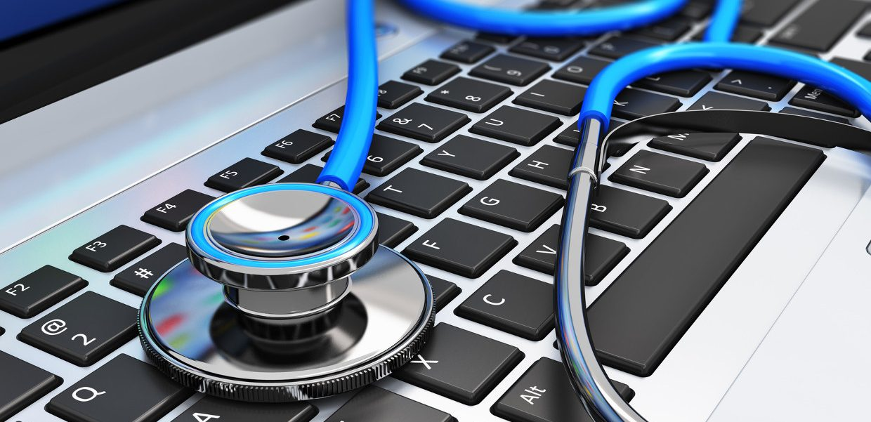 Healthcare and medicine or computer antivirus protection and repair maintenance service concept: macro view of blue stethoscope on business office laptop notebook keyboard with selective focus effect